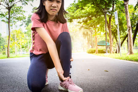 Female teenager hand touching painful twisted or ankle sprain,feel ache,ankle injury after exercise at park,asian child girl have leg pain,problem,accident while running,playing on the street,health care concept