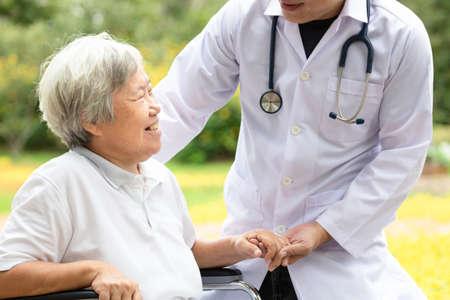 Freundlicher männlicher asiatischer Arzt, der sich erholt, ermutigt, tröstende ältere Patientin, Arzt mit Stethoskop, der die Hand älterer Menschen hält, um bei der Pflege zu helfen, das Sitzen im Rollstuhl im Krankenhaus zu unterstützen, Krankenversicherung, Gesundheitskonzept