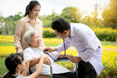 Male asian doctor examining senior woman patient by stethoscope, family doctor checking using stethoscope to listening breath,heart beat sounds lungs of elderly people,general health checkup,health care concept