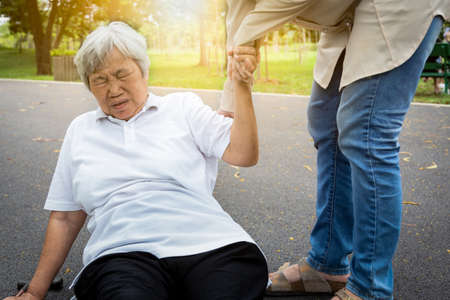 Asian elderly woman fell to the floor after tripped over something, female caregiver or daughter help care to her in nursing home,sick senior mother skid,falling down because of dizziness,faint,suffering from illness,headache,hypertension,health care concept