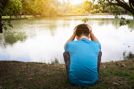 Le marchand en faillite désespère le ralentissement économique dans une grosse dette assise tendu par un homme asiatique lugubre, en pleurs, au chômage, stressé, triste, sombre et la tête baissée, les hommes se sentent stressés et déçus