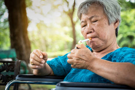 Asian senior woman holding a cigarette smoking,elderly smokers smoking in wheelchair,smoking is dangerous to health,causes various serious diseases,cancer,emphysema,addicted to cigarettes and difficult to quit