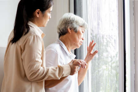 Asian senior woman looking through the window in bedroom,feeling sad and lost; depressed elderly people looking away outside waiting for his family to visit at nursing home,facial expression,life depression,nostalgia concept