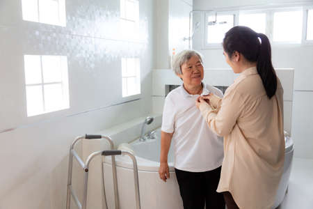 Asian daughter or female caregiver taking off the clothes of senior mother before taking a shower in bathroom,help,support,take care closely,concerned about the safety of elderly woman,prevent slippery and accidents in the bathroom at home 免版税图像