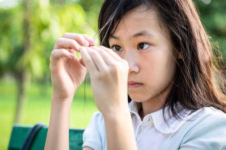 Bella bambina asiatica che si tira i capelli con le dita in problemi di salute mentale, sistema nervoso, sistema cerebrale o schizofrenia, paziente psichiatrica femminile con disturbo da tricotillomania Archivio Fotografico