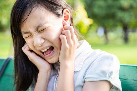 Donna infastidita che copre le orecchie con gli indici si sente ferita dolore all'orecchio dolore otite da rumore forte, musica rumorosa o ansia bambina asiatica con schizofrenia che non vuole sentire cose spiacevoli soffre di dolore mentale, sente cose