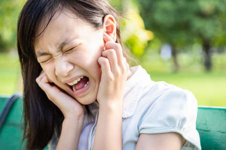 Verärgerte Frau, die die Ohren mit den Zeigefingern bedeckt, fühlt sich verletzt Ohrenschmerzen Schmerzen Otitis durch laute Geräusche, laute Musik oder Angst