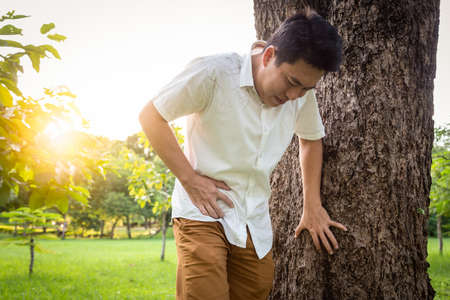 Asian man touching stomach painful in the right side attack of appendicitis, male patient suffering from stomachache feeling acute pain,appendicitis symptoms in nature at outdoor park,healt care concept Stock Photo