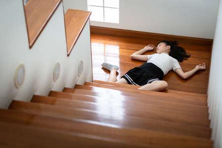Niña asiática en coma en el piso que se siente inconsciente después de un accidente, se cae de una escalera, una adolescente enferma se cae o se resbala al piso debido a mareos, desmayo, enfermedad, situación peligrosa en el hogar