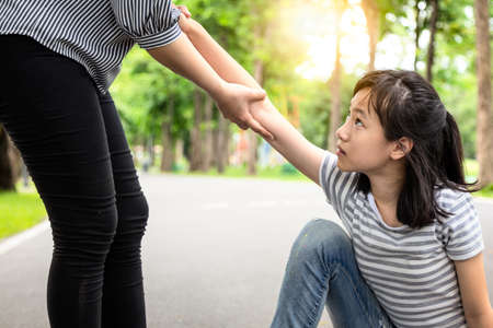 Passerby helping to support the child girl to stand up from on the floor after falling down at park,asian woman pulling hand and give encouragement to female teenage,kindness,friendship concept 版權商用圖片