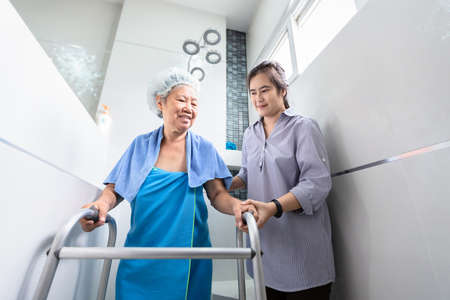 Asian daughter or female care assistant service,help,support senior woman taking a shower in bathroom,happy mother walking with walker in bathroom at home,safety of elderly people and family relationships concept