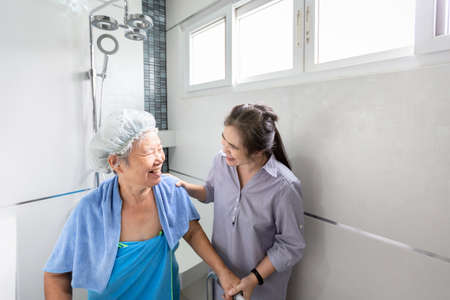 Asian daughter or female care assistant service,help,support senior woman taking a shower in bathroom,take care closely,happy mother is difficult to help herself,concerned about the safety and accidents of elderly people at home 免版税图像