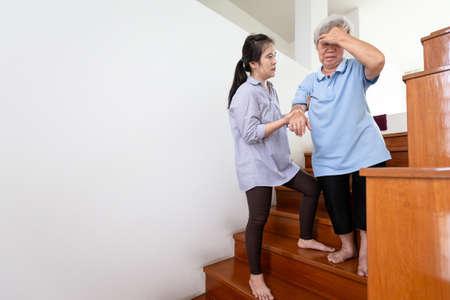 Madre mayor asiática que tiene presión arterial, vértigo, mareos mientras baja la escalera, dolor de cabeza de anciana enferma, se siente débil, hija o asistente de atención, ayuda, apoyo en el hogar, concepto de atención médica