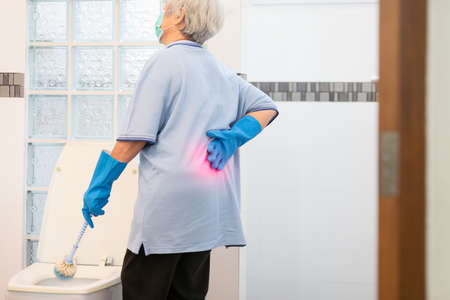 Asian senior woman in blue glove,cleaning toilet bowl,female elderly housekeeper hands touching back pain having backache,muscle,hip pain or waist pain while housework,wash the bathroom at home,health problems concept