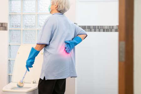 Femme âgée asiatique en gant bleu, nettoyage de la cuvette des toilettes, mains de femme de ménage âgée touchant des maux de dos ayant des maux de dos, des douleurs musculaires, des hanches ou des douleurs à la taille pendant les travaux ménagers, laver la salle de bain à la maison, concept de problèmes de santé