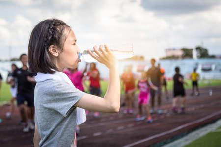 Porträt eines asiatischen Kindermädchens, das eine Flasche Wasser hält, Wasser aus einer Plastikflasche unter dem Sonnenlicht trinkt, eine Sportlerin, die eine Pause macht und nach dem Laufen Wasser trinkt, um den Schweißverlust auszugleichen und ihren Durst an einem heißen sonnigen Tag im Freien im Stadion zu reduzieren Standard-Bild