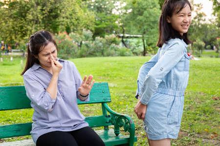 Asiatisches Tochtermädchen, das ihren Hintern mit gebrochenem Wind hält, den ganzen Tag furzt, schlechter Geruch und stinkt durch Blähungen, Blähungen und Gas im Verdauungstrakt, während die Mutter seine Nase bedeckt, stinkender Furz