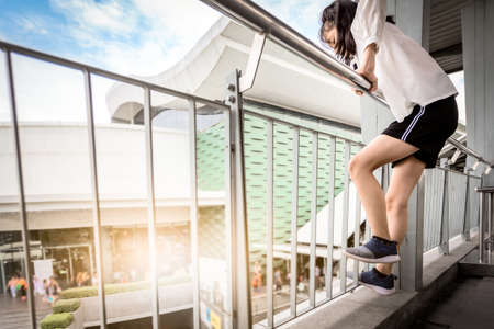 Sad asian teenager girl stand on the footbridge with a suicidal ideation and contemplating to commit suicide by jump the bridge,depression woman with suicide decisions are caused by family problems,toxic shame,depressive concept