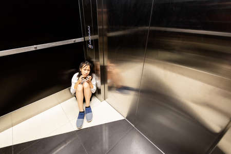 Anxiety asian child girl having panic disease attack in an elevator,stressful depressed teenage girl with mental health illness and narrow fears,suffocation, heart palpitation suffer from panic disorder Stok Fotoğraf