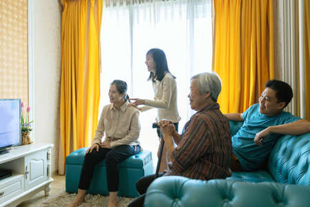 Happy asian family,father,mother,daughter,and senior grandmother relaxing,watching movies dramas series on TV,enjoying watch television and laughing in living room at home,lifestyle,weekend activities
