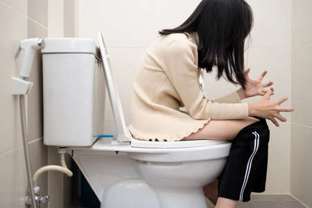 Asian child girl sitting on toilet with her pants down in the bathroom with suffering from constipation,diarrhea or hemorrhoids,anxiety woman feel painful stomach,couldn't get the poo out,health care Standard-Bild - 134653367