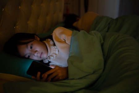 Asian child girl watch movie on smartphone in bedroom,female teenage lying in bed at night time and playing game or chatting on mobile phone,addict social networks,technology,communication concept Zdjęcie Seryjne