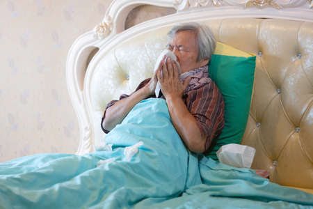 Sick senior have a cold,blowing nose in paper handkerchief  in bedroom,flu or the weather is changing,asian elderly sneezing in a tissue paper,concept of allergic rhinitis,dust allergy and health care