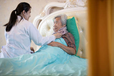Family medical female doctor or nurse checking heart and lungs of senior patient using stethoscope in bed at home,asian caregiver examining elderly woman,health care,medical checkup,medicine  concept Standard-Bild - 134653374