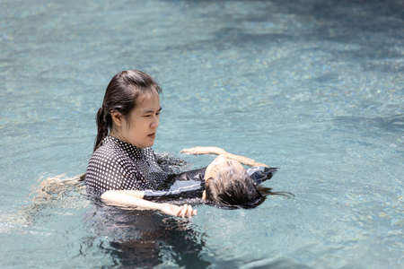 Asian child girl drowning in underwater,drowning female teenager in swimming pool,mother rescuing unconscious daughter drowning in swimming pool in dangerous situation,concept of safety