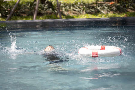 Asian child girl struggling for a life buoy in swimming pool to rescue drowning in dangerous situation in summer vacation, lifebuoy or ringbuoy equipment for save life in water, concept of safety