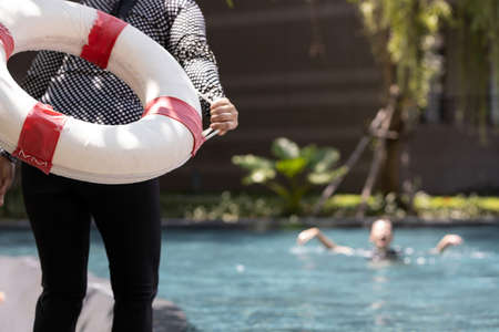 Person hand holding ringbuoy to rescue drowning in dangerous situation on summer vacation,asian child girl struggling in water, female people throwing lifebuoy help woman drowning in swimming pool Zdjęcie Seryjne