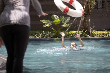 Mother is saving the life of a teenager daughter using ringbuoy to rescue drowning in dangerous situation; asian child girl struggling; asking for help in water; female people throwing lifebuoy help woman drowning in swimming pool; concept of safety