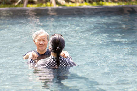 Asian daughter is supporting,care the elderly mother walking in pool on sunny day and exercising in the morning ,happy and healthy senior woman in swimming pool in summer vacation,health care concept Zdjęcie Seryjne