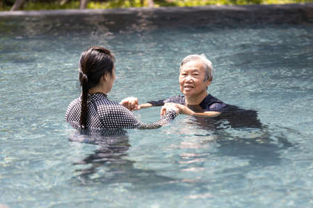 Asian caregiver woman is support,care the elderly people walking,exercising in the water,happy and healthy senior mother in swimming pool with daughter in sunny day,healthcare,physical therapy concept