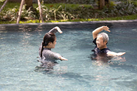Asian physiotherapist is supporting,care the elderly people doing water aerobics,exercising in pool,happy and healthy senior mother in swimming pool with daughter,health care,physical therapy concept