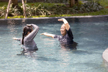 Asian daughter is support,care the elderly mother doing water aerobics in sunny day and exercising in the morning,happy and healthy senior woman in swimming pool in summer vacation,health care concept