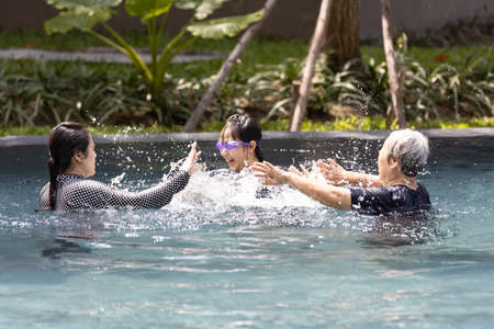 Happy asian family having fun in swimming pool in summer vacation,mother and daughter playing with her senior grandmother is enjoy,laughing,family time among generations,family relationships concept