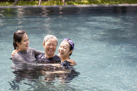 Happy asian family having fun and hug in swimming pool,smiling mother and child girl daughter playing with her senior grandmother is enjoy,laughing in outdoor sunny day,family relationships concept Standard-Bild - 134653432