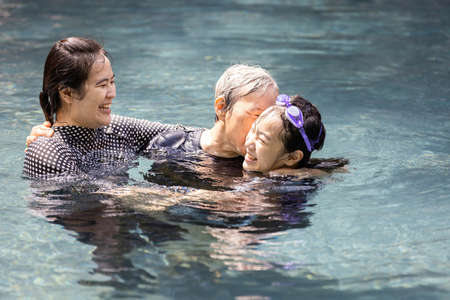 Happy asian family having fun,enjoy in swimming pool,smiling mother and daughter laughing,playing with her senior grandmother, elderly kissing on cheek of child girl, love,family relationships concept