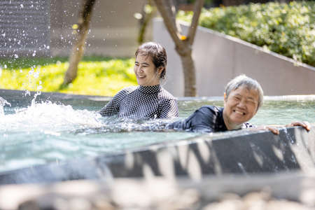 Happy asian woman help, care senior people in swimming pool,healthy elderly mother exercising,learns to swim in pool with smiling trainer or daughter in outdoor on sunny day,feeling relax,health care Standard-Bild - 134653434