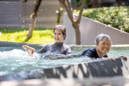 Happy asian senior people and young woman having fun,enjoy together in swimming pool,healthy elderly mother exercising,learns to swim in pool with smiling trainer or daughter, health care concept Standard-Bild - 134653435