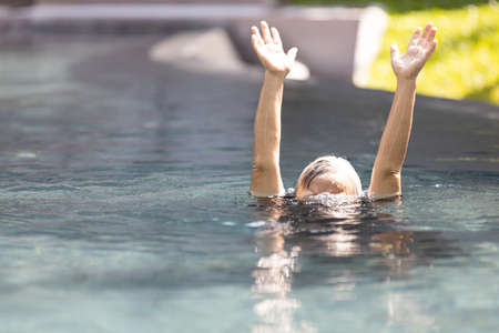 Asian senior people struggling underwater, hand peeking out of the water, female drowned in swimming pool, drowning elderly woman in swimming pool asking for help in dangerous situation Standard-Bild - 134653436