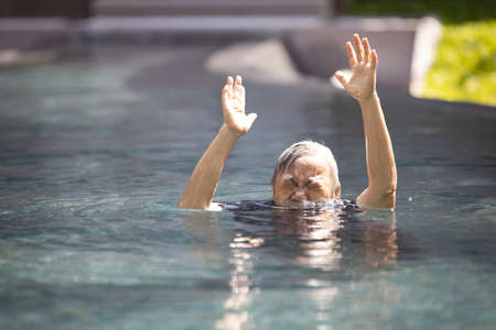 Asian senior people struggling underwater, hand peeking out of the water, female drowned in swimming pool, drowning elderly woman in swimming pool asking for help in dangerous situation Banque d'images