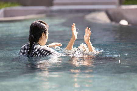 Asian senior people struggling underwater,woman drowned in water,drowning female elderly person in swimming pool asking for help,daughter rescuing unconscious mother drowning in swimming pool