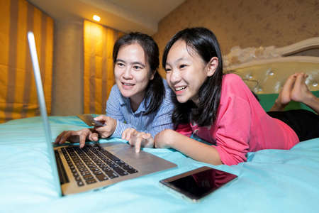 Happy mother and her daughter enjoy using laptop computer with shopping online surfing the internet in bedroom at home,smiling asian woman and child girl in front of the notebook and serf web-sites Standard-Bild - 134653496