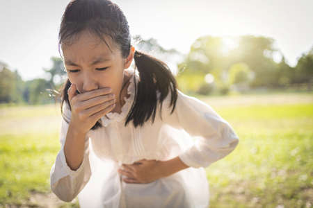 Asian beautiful child girl covered her mouth about to throw up,vomit,puke retch barf,female teenage feel sick from indigestion or food poisoning,stomach upset virus in sunny day,health care concept Standard-Bild - 134653501