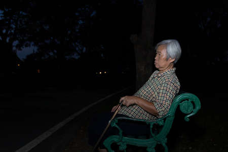 Asian senior woman sitting on a bench at night alone, elderly people confusion with time or place ,memory loss suffer age-related,female patient with dementia or alzheimer's disease in the park
