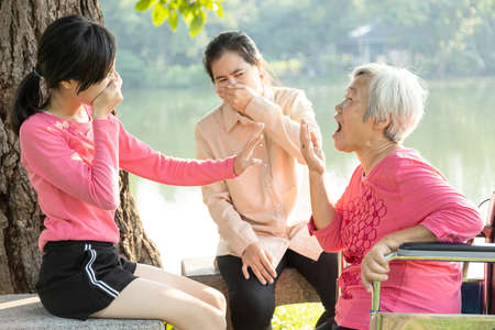 Asian senior grandmother talking to her family and checking breath with her hand,elderly people bad breath,daughter,granddaughter closing her nose, girl feel stinks,very bad smell,dental care concept Zdjęcie Seryjne
