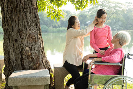 Asian daughter,granddaughter closely take care of the senior mother,smiling child girl talk fun together,happy elderly woman in wheelchair enjoying,relax with her family in sunny day,family vacation