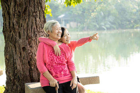 Happy old elderly woman and child girl laughing,embracing in outdoor park on sunny day,loving senior grandmother,smiling teenage granddaughter enjoy, relax on holiday together,health care,generation,lifestyle